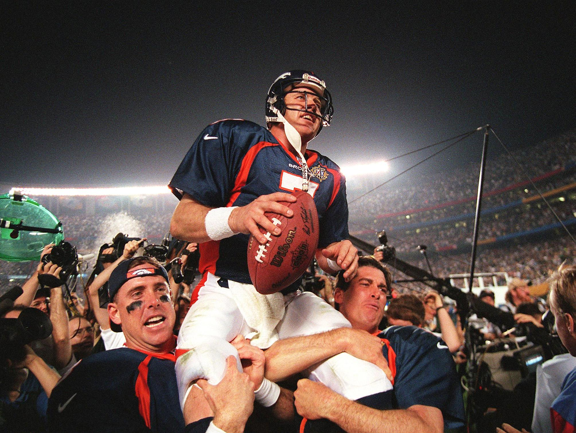 Denver Broncos quarterback John Elway (C) is carried by teammates Ed McCaffrey (L) and Bubby Brister (R) after the Broncos defeated the Green Bay Packers 31-24 to win Super Bowl XXXII in San Diego, CA 25 January. (credit: TIMOTHY A. CLARY/AFP/Getty Images)
