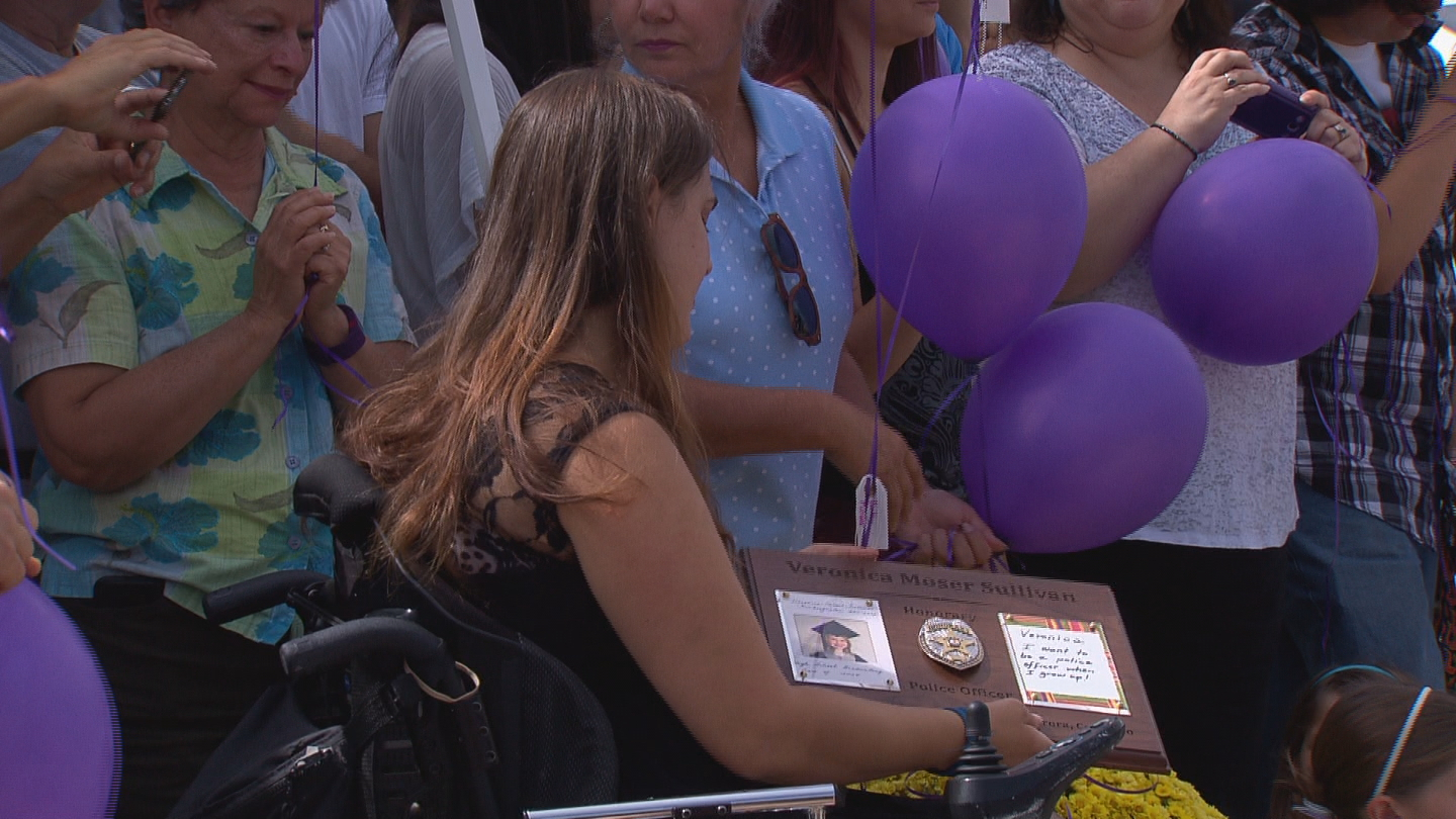 Veronica Moser-Sullivan's mother Ashley Moser looks at the plaque presented by Aurora Police on Saturday (credit: CBS)