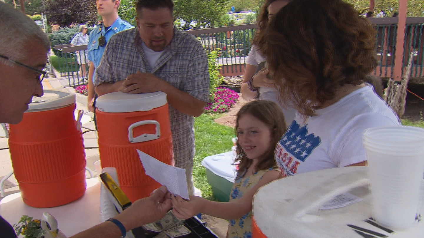 Aubrey Dearman is presented a check for her lemonade stand by Aurora Police (credit: CBS)