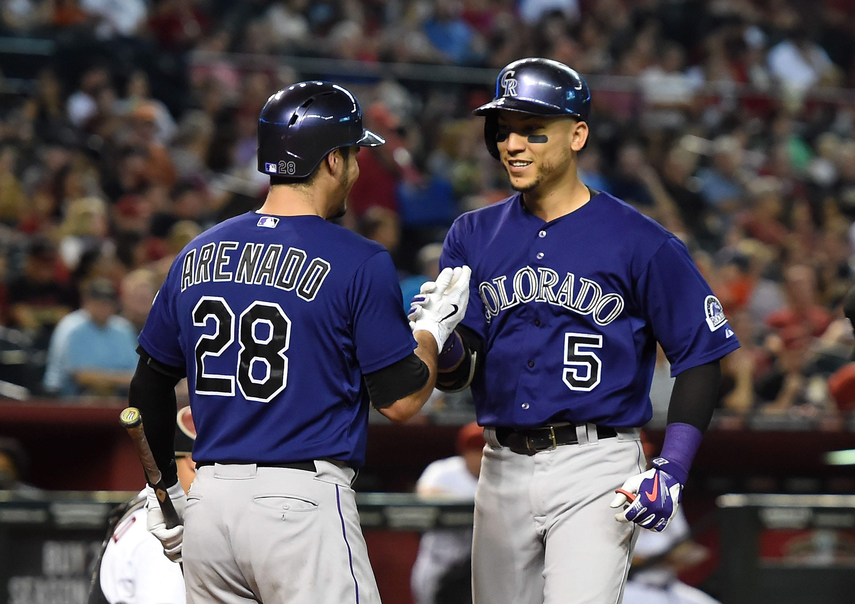 Carlos Gonzalez of the Colorado Rockies celebrates with teammate Nolan Arenado after hitting a third inning home run against the Arizona Diamondbacks at Chase Field on Sept. 29, 2015. (Photo by Norm Hall/Getty Images)