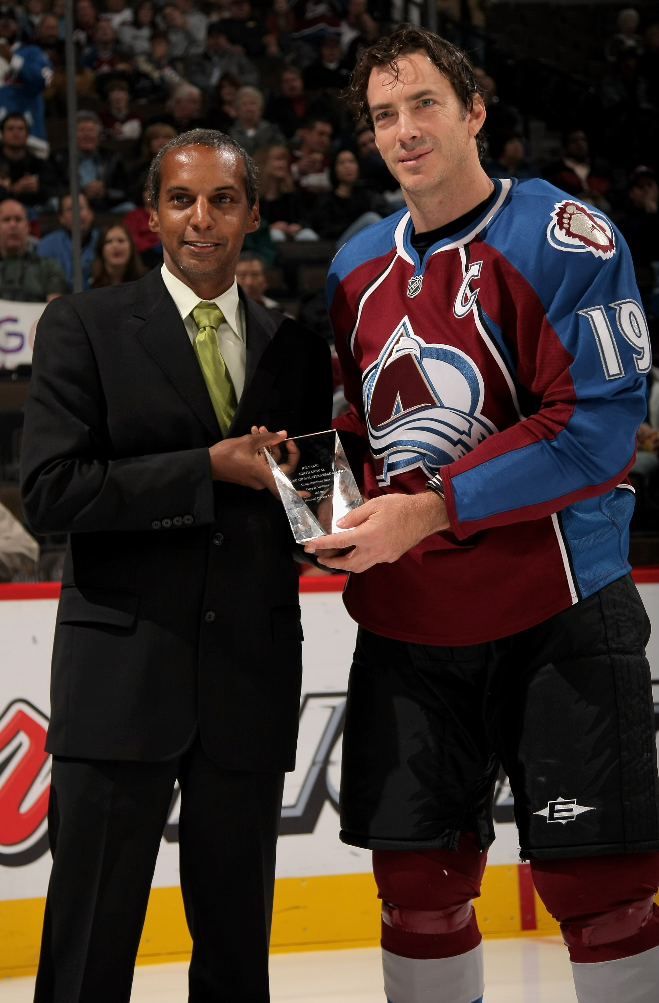 Kenneth Martin, Jr., NHL vice president of community and diversity programming, awards Joe Sakic #19 of the Colorado Avalanche the 2007 NHL Foundation Player Award prior to a game against the Calgary Flames at the Pepsi Center on October 16, 2007. (Photo by Doug Pensinger/Getty Images)
