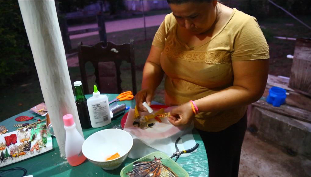 A woman making jewelry from lionfish (credit: CBS)