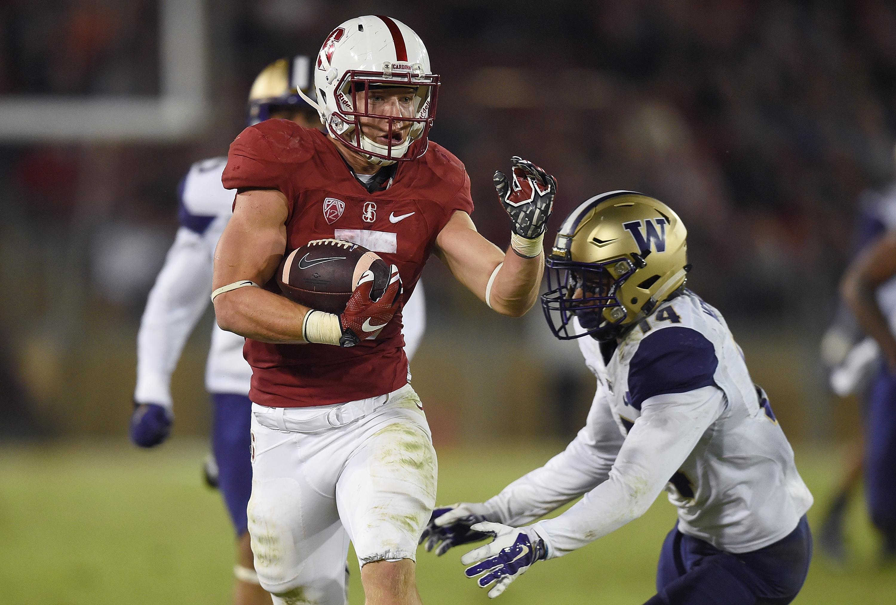 Christian McCaffrey #5 of the Stanford Cardinal's scores a touchdown breaking the tackle of JoJo McIntosh #14 of the Washington Huskies in the third quarter of an NCAA football game at Stanford Stadium on October 24, 2015 in Stanford, California. (Photo by Thearon W. Henderson/Getty Images)
