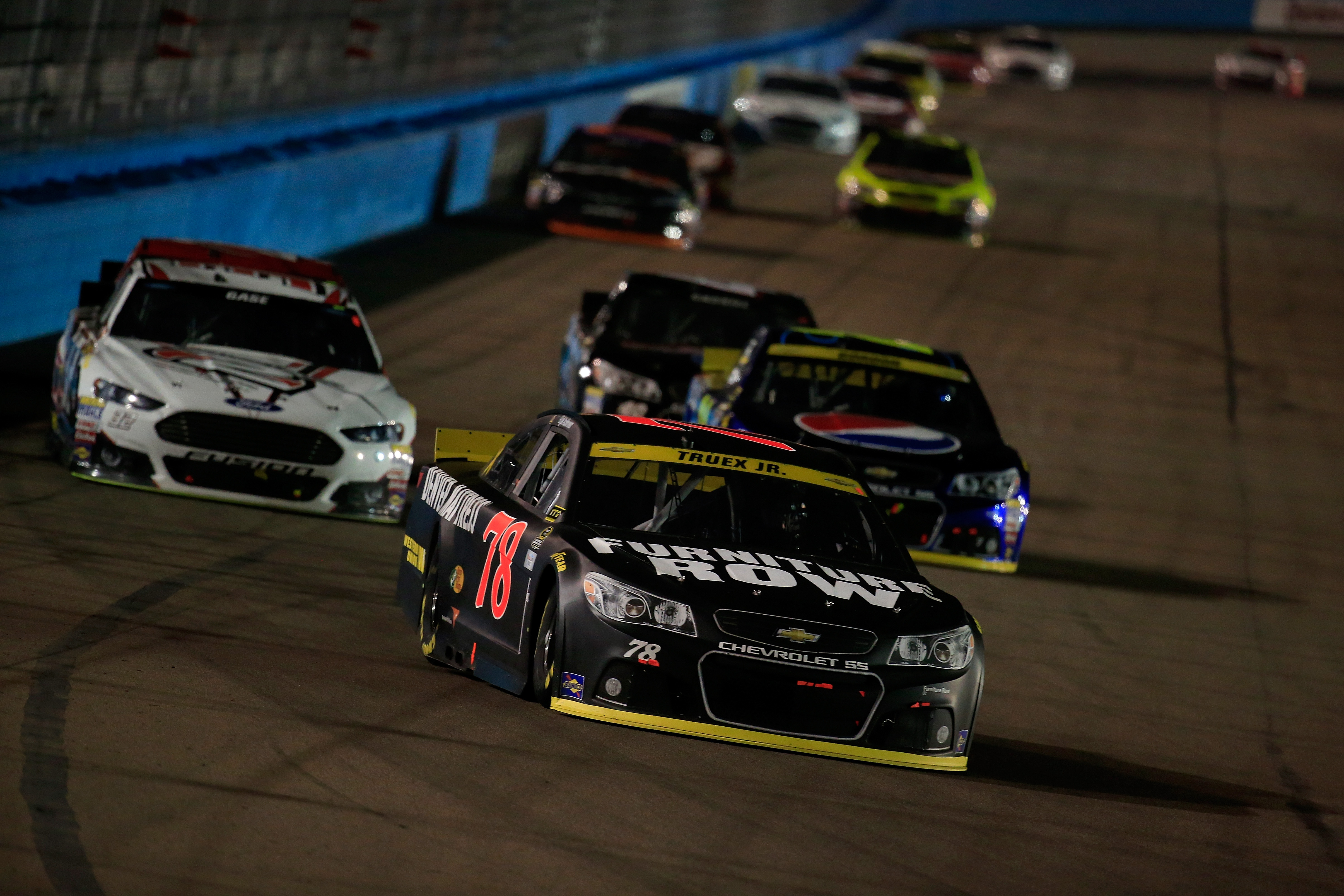 Martin Truex Jr., driver of the #78 Furniture Row/Visser Precision Chevrolet, races Jeff Gordon, driver of the #24 Pepsi Chevrolet, during the NASCAR Sprint Cup Series Quicken Loans Race for Heroes 500 at Phoenix International Raceway on November 15, 2015 in Avondale, Arizona.  (Photo by Chris Trotman/Getty Images)