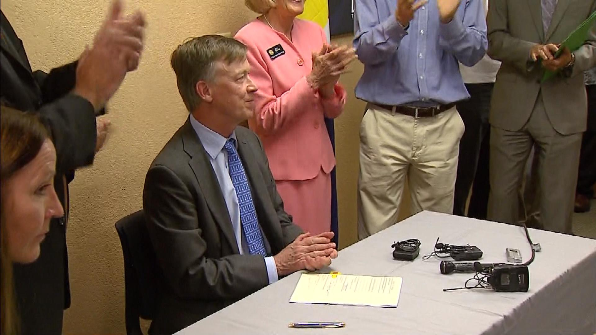 Gov. Hickenlooper signing the bill into law (credit: CBS)