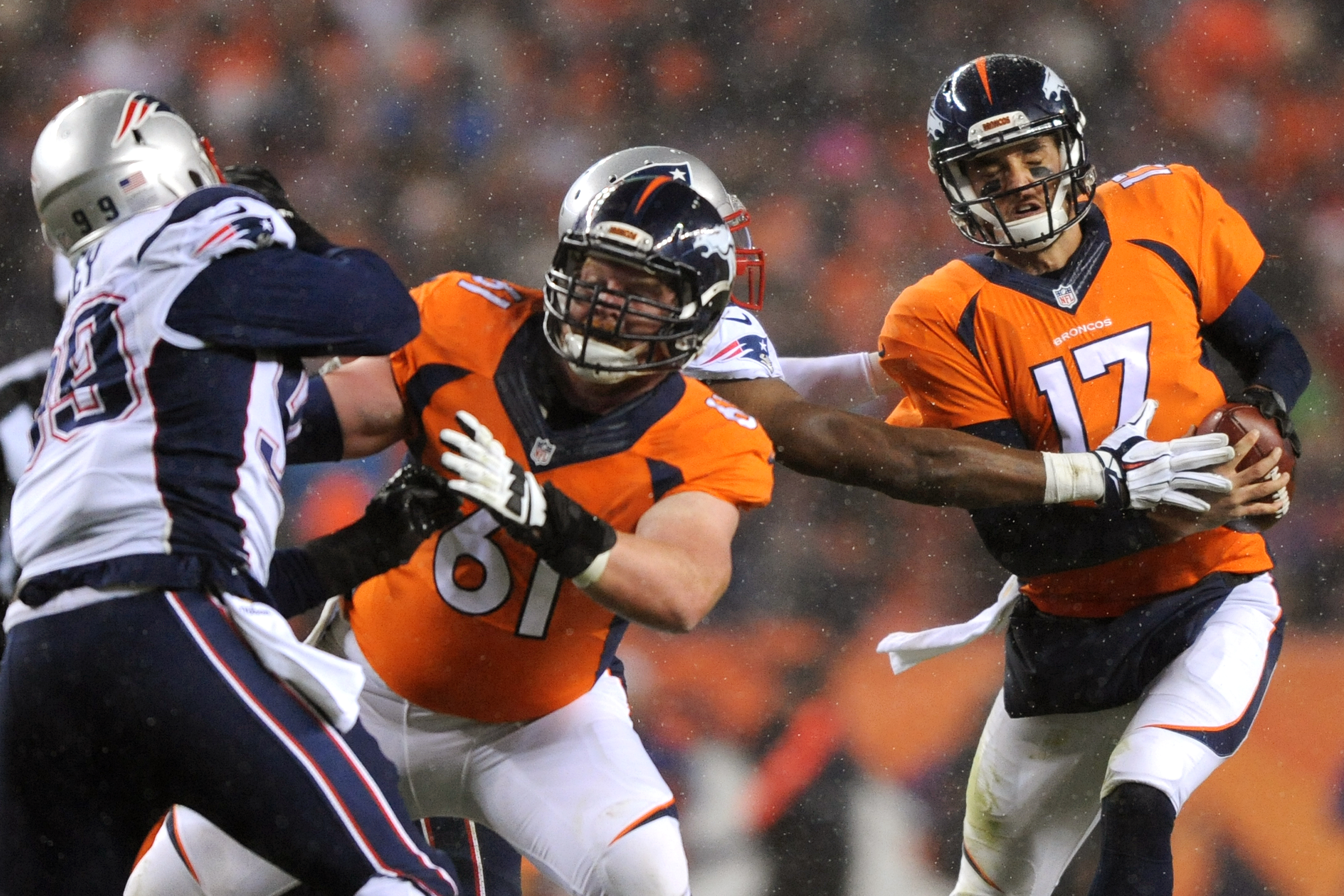 Quarterback Brock Osweiler #17 of the Denver Broncos scrambles while center Matt Paradis #61 of the Denver Broncos blocks against defensive tackle Dominique Easley #99 of the New England Patriots in the first quarter at Sports Authority Field at Mile High on November 29, 2015 in Denver, Colorado. (Photo by Dustin Bradford/Getty Images)