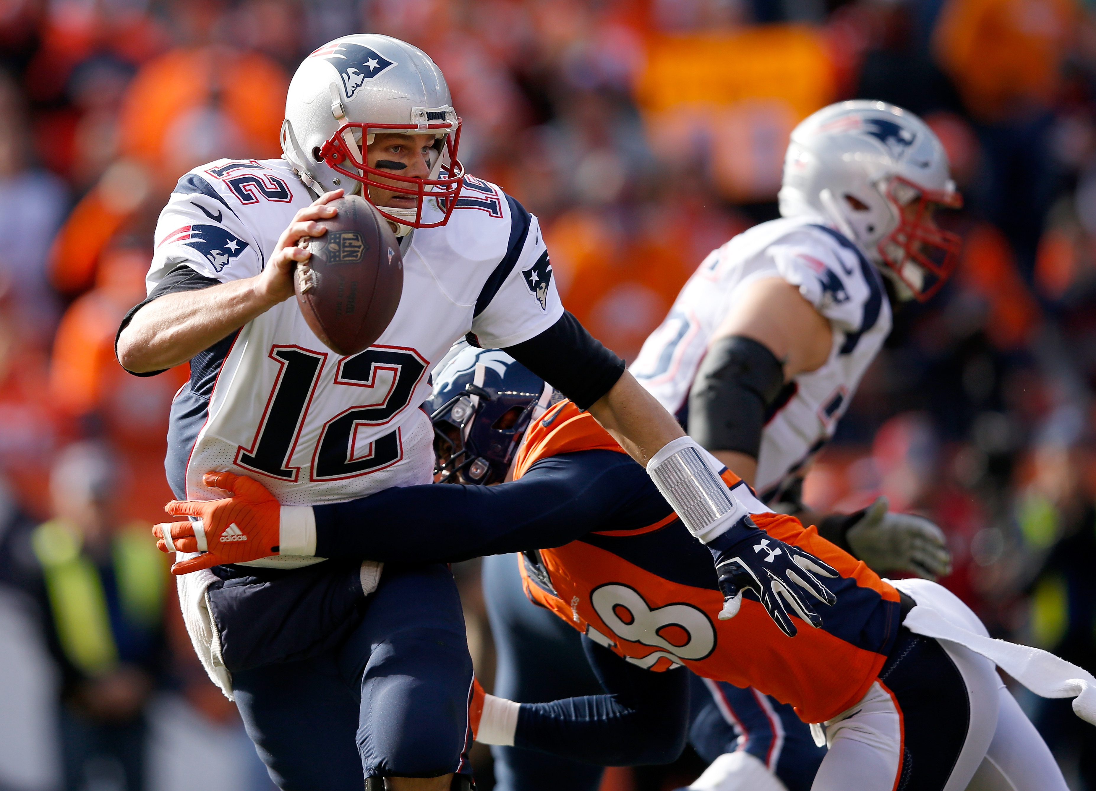 Tom Brady #12 of the New England Patriots tries to evade a tackle by  Von Miller #58 of the Denver Broncos in the first half in the AFC Championship game at Sports Authority Field at Mile High on January 24, 2016 in Denver, Colorado.  (Photo by Ezra Shaw/Getty Images)