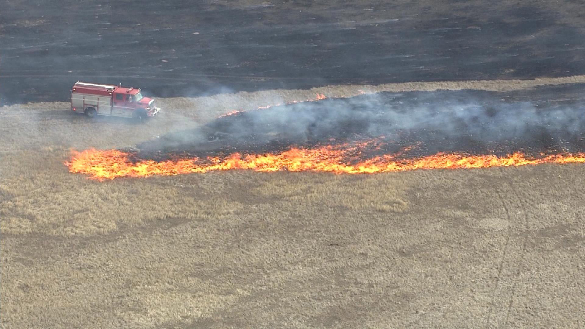 Firefighters battle a grass fire in rural Weld County on Feb. 18. (credit: CBS)