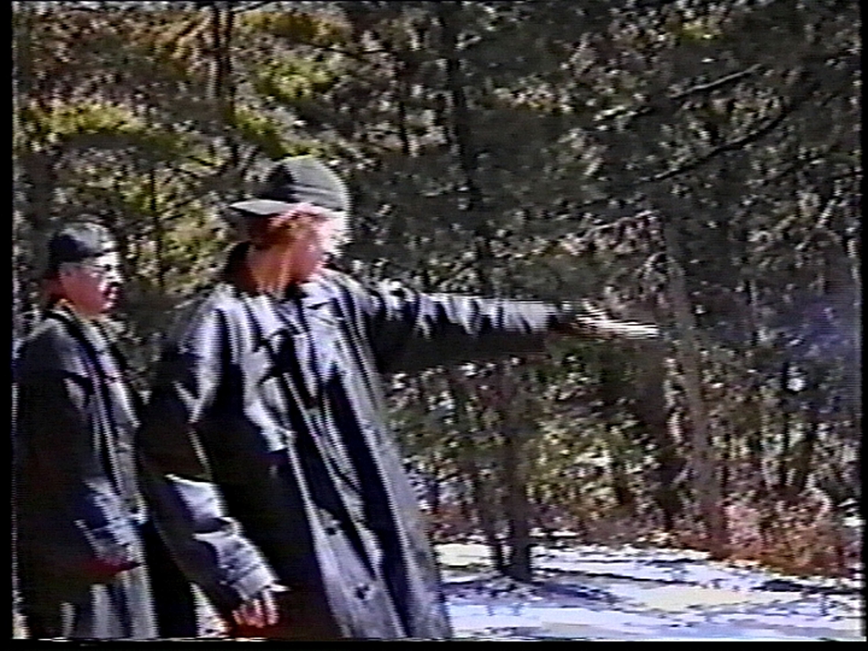 Eric Harris (L) watches as Dylan Klebold practices shooting a gun at a makeshift shooting range March 6, 1999 in Douglas County, CO in this image from video released by the Jefferson County Sheriff's Department. Approximately six weeks after this video was made, Klebold and Harris killed 13 people at Columbine High School in Littleton. Some of the weapons seen in the video were used in the shooting. (credit: Jefferson County Sheriff's Department via Getty Images)