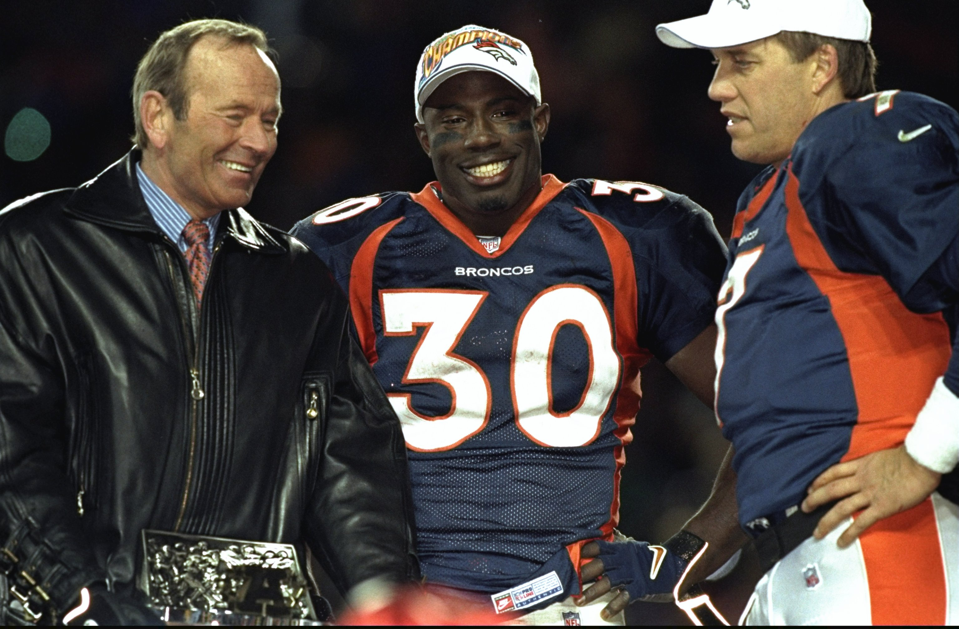 Terrell Davis of the Denver Broncos stands with Broncos owner Pat Bowlen, left, and John Elway, right, after winning the AFC Championship Game in 1999 against the New York Jets at Mile High Stadium (credit: Brian Bahr /Allsport)