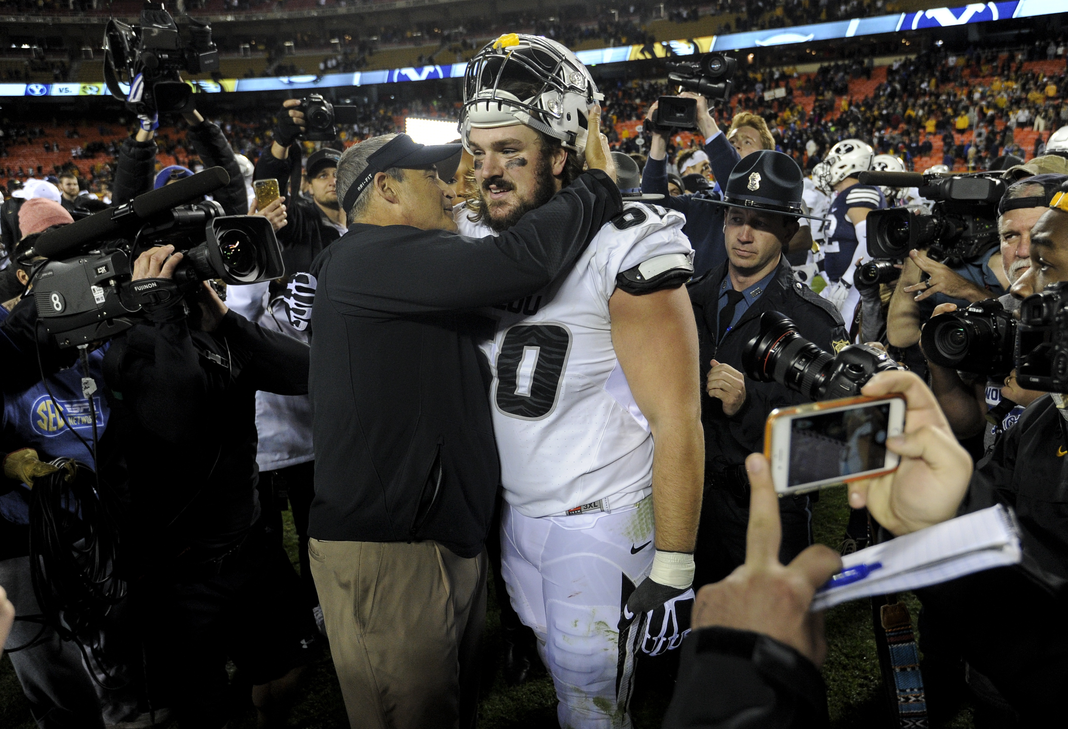Head coach Gary Pinkel of the Missouri Tigers hugs Connor McGovern #60 after a 20-16 win over the Brigham Young Cougars at Arrowhead Stadium on November 14, 2015 in Kansas City, Missouri. (Photo by Ed Zurga/Getty Images)