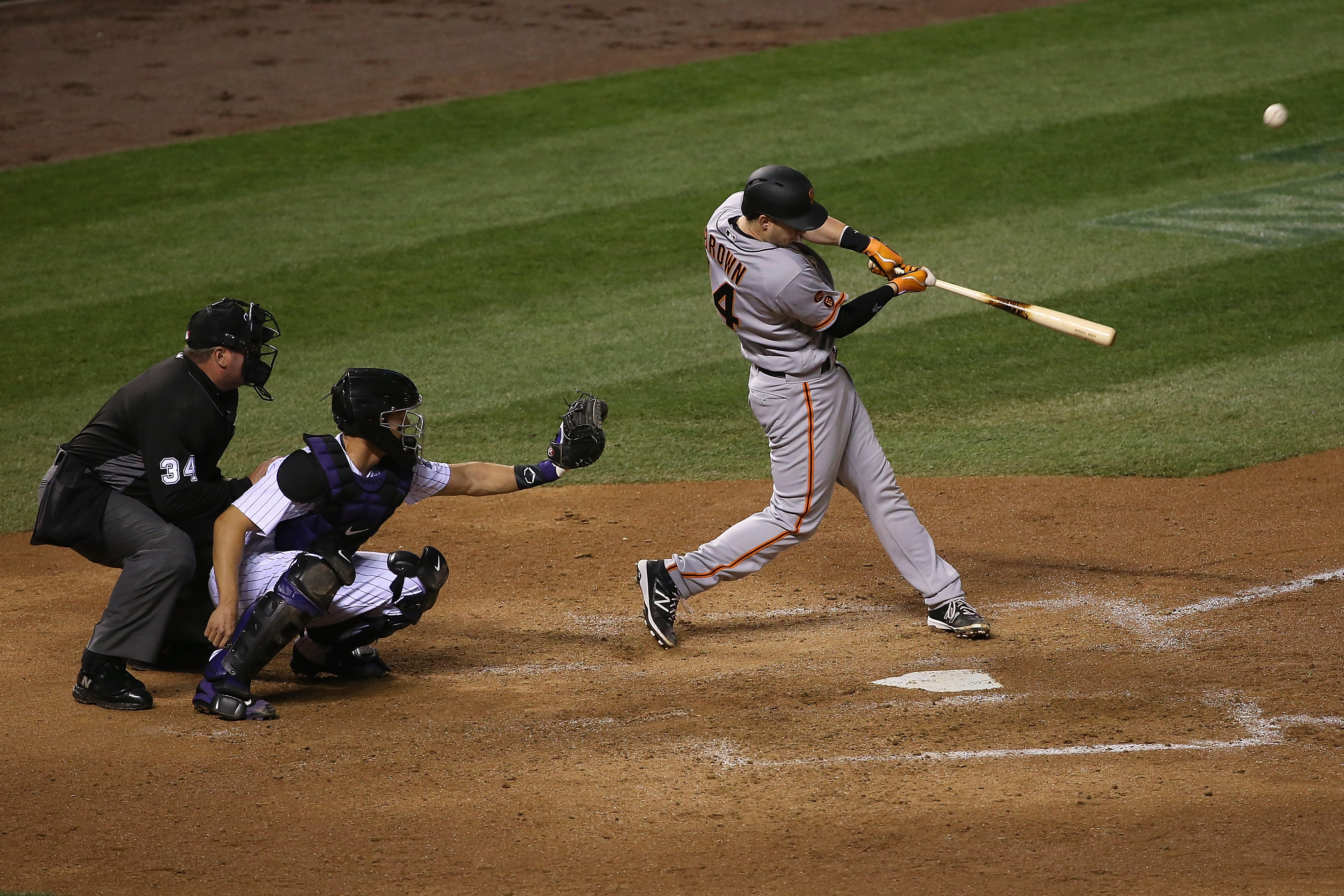 Trevor Brown #14 of the San Francisco Giants hits a two run home run off of Tyler Chatwood #32 of the Colorado Rockies as catcher Nick Hundley #4 of the Colorado Rockies backs up the plate and umpire Sam Holbrook oversees the action as the Gaints take a 5-2 in the sixth inning at Coors Field on April 12, 2016 in Denver, Colorado.