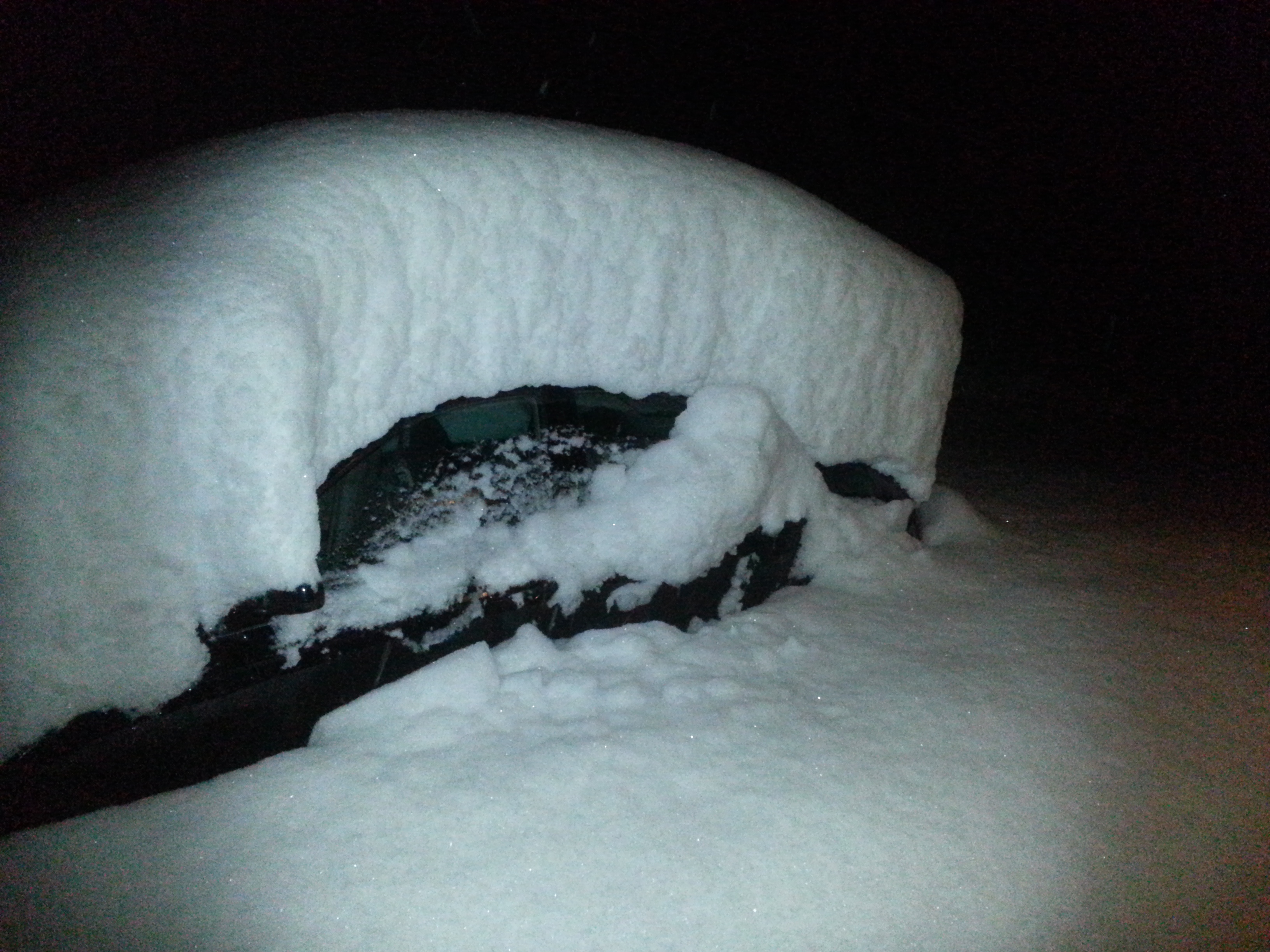 A snow-covered car in Kittredge after 2 feet of snow fell overnight during an April storm. (credit: Kerry Maloney)
