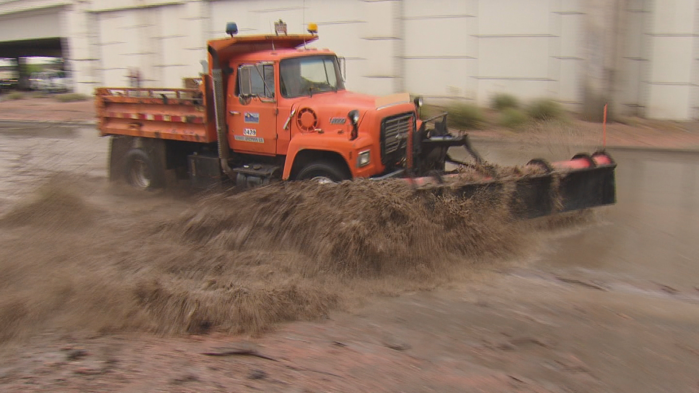 Snowplows worked to clear the standing water from I-25 and Broadway (credit: CBS)