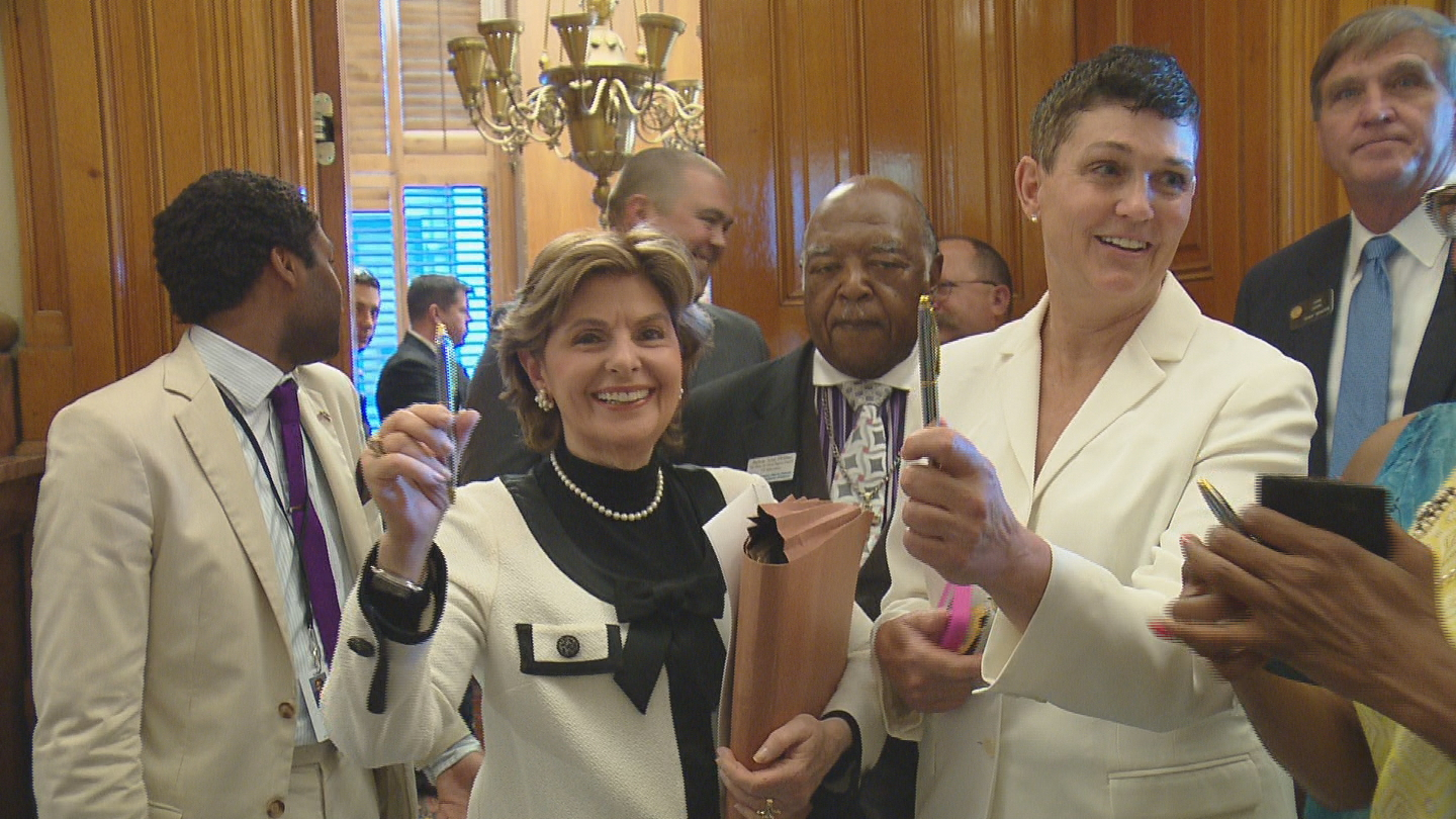 Attorney Gloria Allred and Beth Ferrier show off their pens after the bill signing on Friday (credit: CBS)