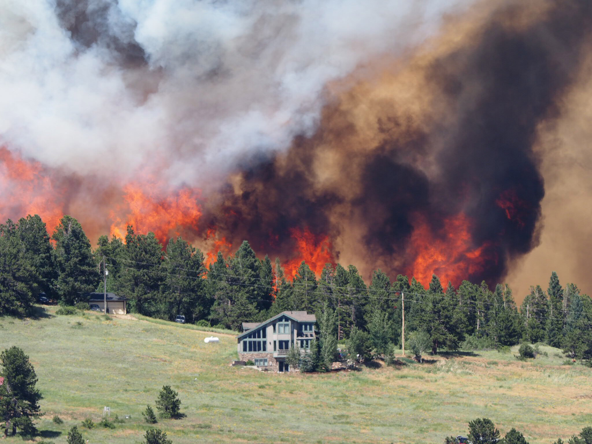 John and Annie Bonvoulior's home in the foreground of the Cold Springs Fire (credit: Joe McManus)