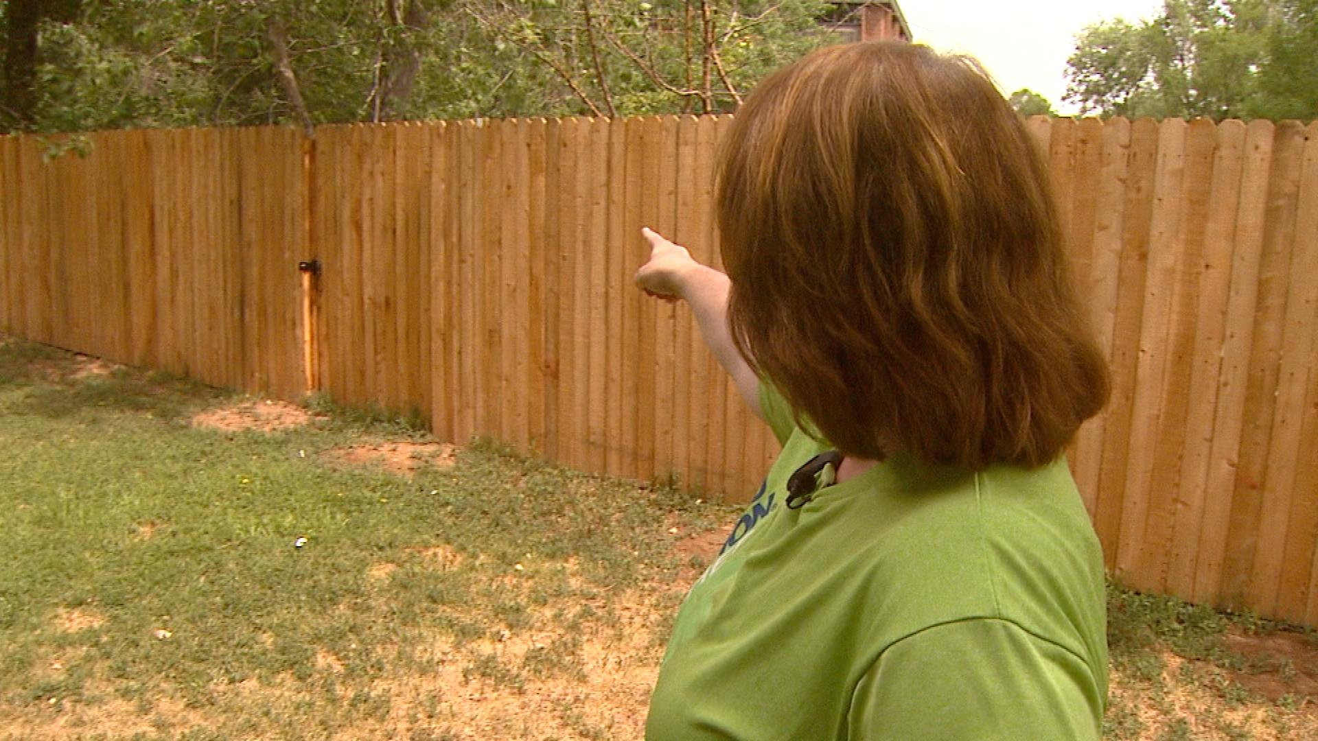 Debra Gania points to where the coyote jumped her tall fence (credit: CBS)