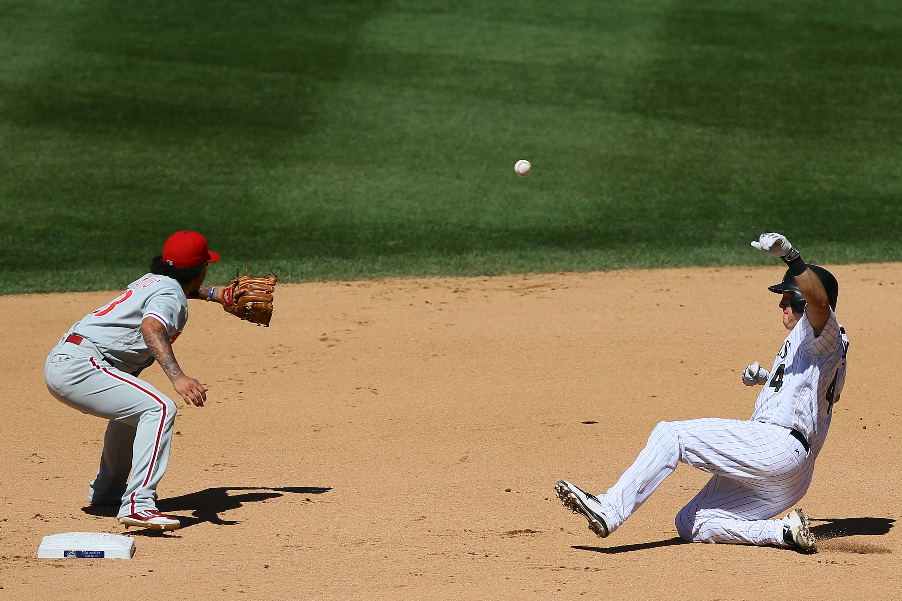 Nick Hundley #4 of the Colorado Rockies slides in safely for a double ahead of the baseball as Freddy Galvis #13 of the Philadelphia Phillies awaits the throw during the fourth inning at Coors Field on July 10, 2016 in Denver, Colorado. (Photo by Justin Edmonds/Getty Images)