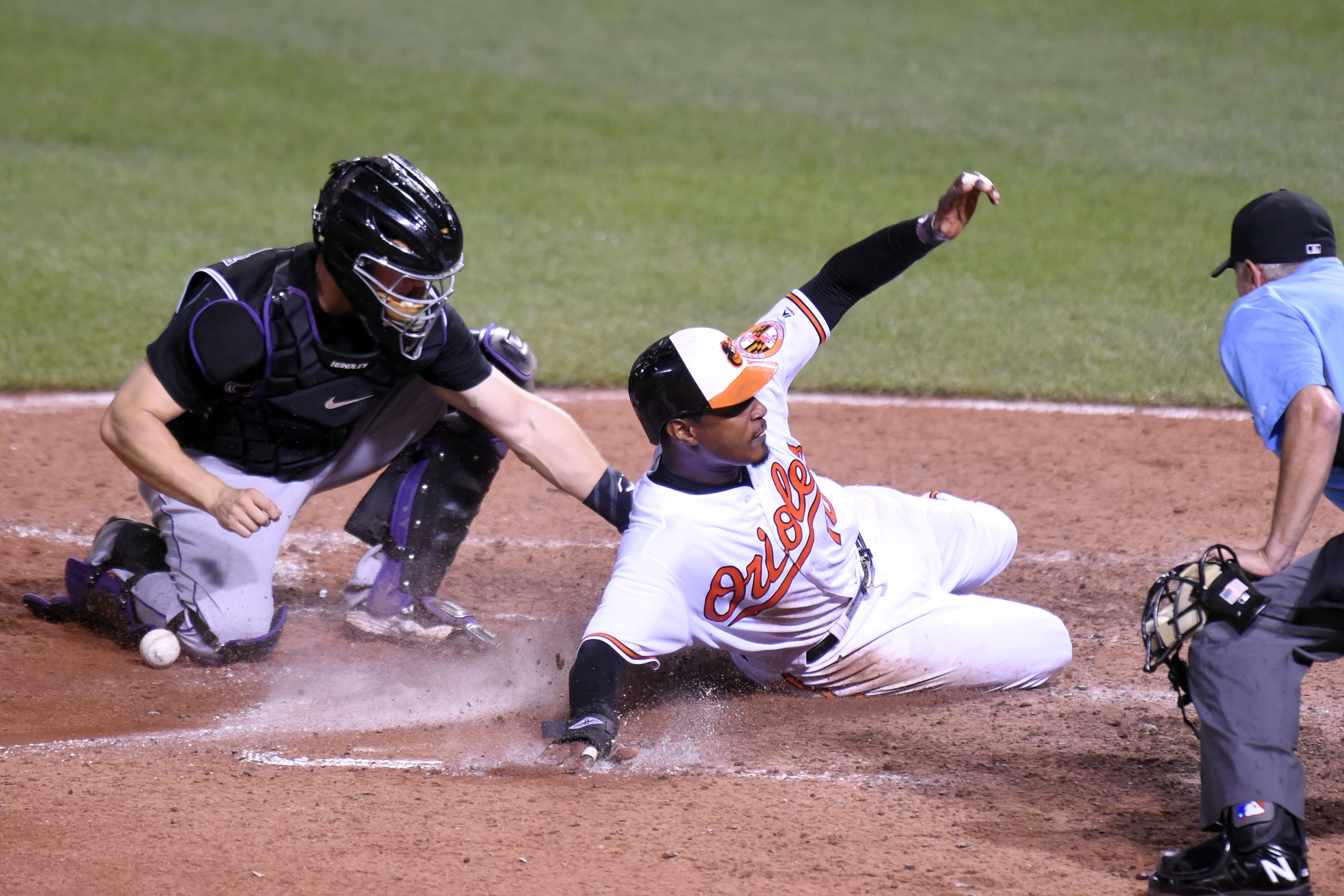 Adam Jones #10 of the Baltimore Orioles beats the tag from Nick Hundley #4 of the Colorado Rockies fromm the winning run during a baseball game at Oriole Park at Camden Yards on July 25, 2016 in Baltimore, Maryland. The Orioles won 3-2 in 10 inning. (Photo by Mitchell Layton/Getty Images)