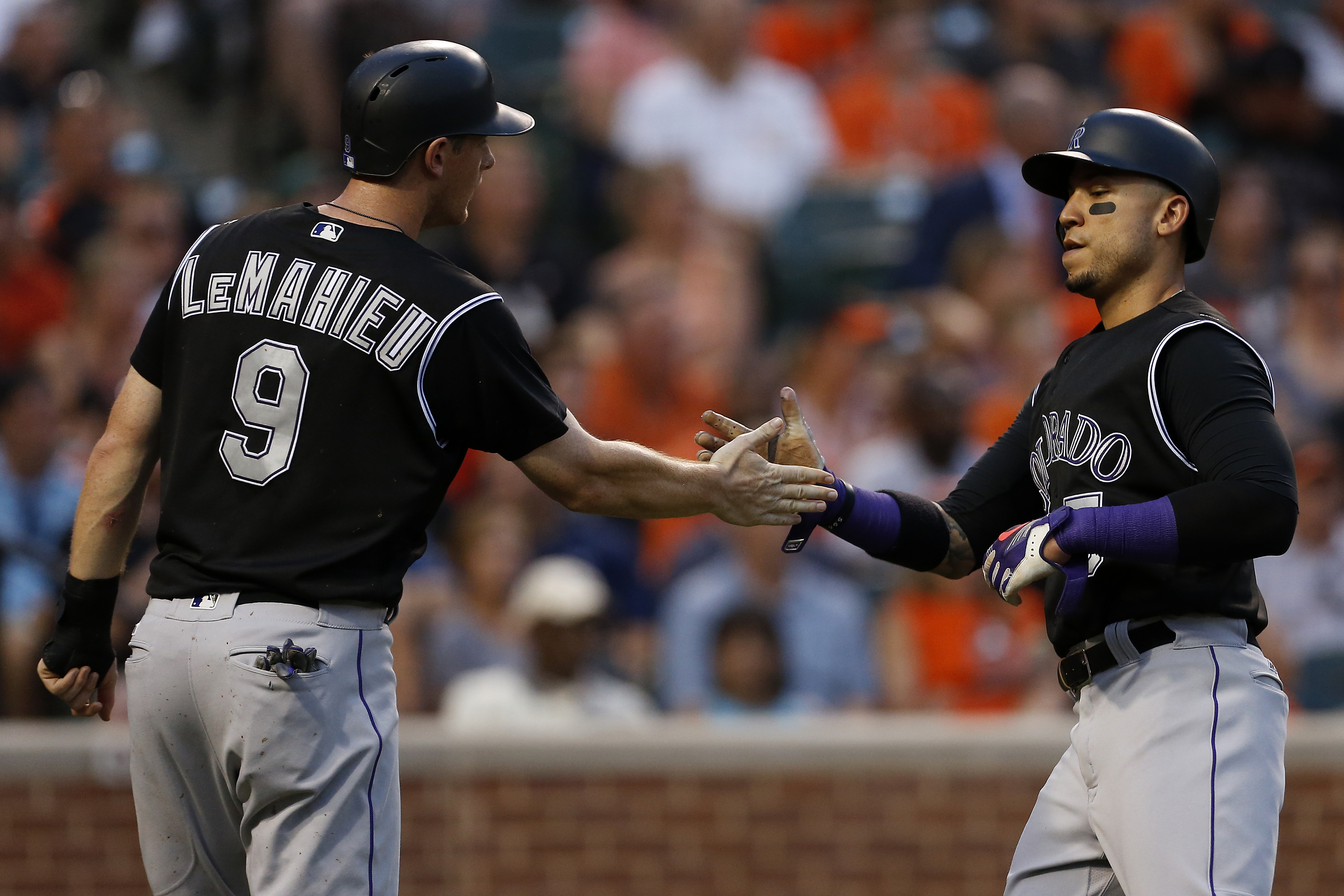 Carlos Gonzalez #5 of the Colorado Rockies celebrates with teammate DJ LeMahieu #9 after scoring in the third inning against the Baltimore Orioles at Oriole Park at Camden Yards on July 26, 2016 in Baltimore, Maryland. (Photo by Matt Hazlett/Getty Images)