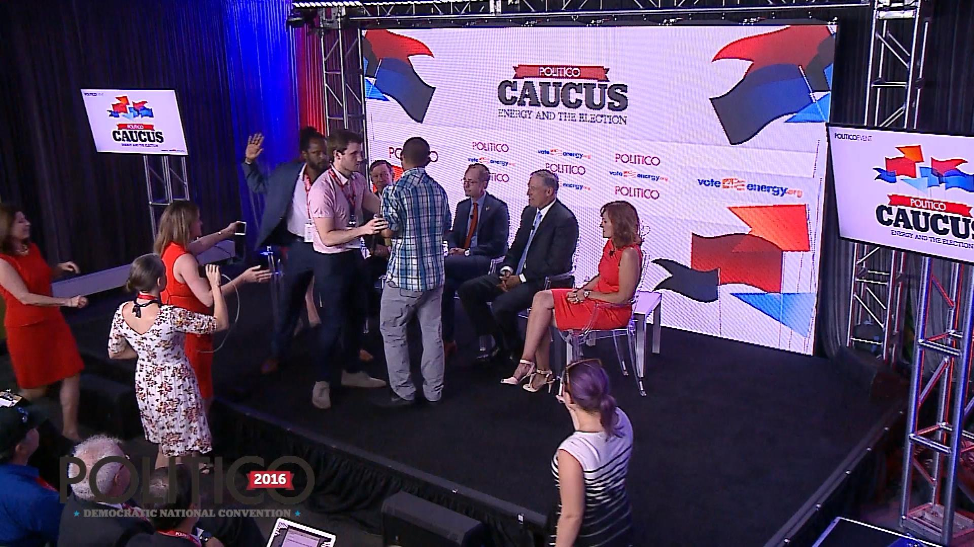 A protester confronting Gov. John Hickenlooper is escorted off the stage (credit: CBS)