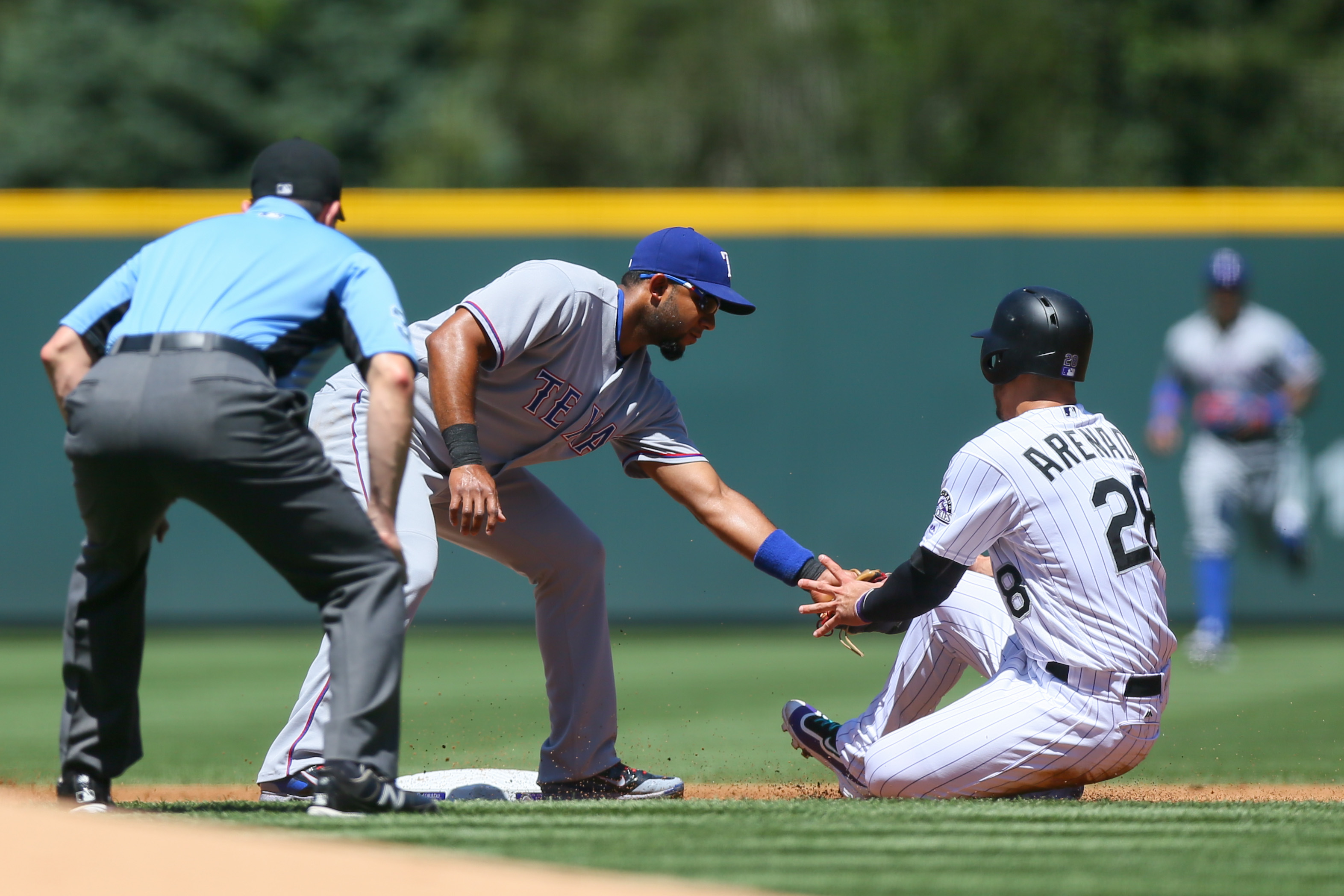 Nolan Arenado #28 of the Colorado Rockies is tagged out by Elvis Andrus #1 of the Texas Rangers in a rundown as umpire Carlos Torres looks closely during the first inning at Coors Field on August 9, 2016 in Denver, Colorado. (Photo by Justin Edmonds/Getty Images)