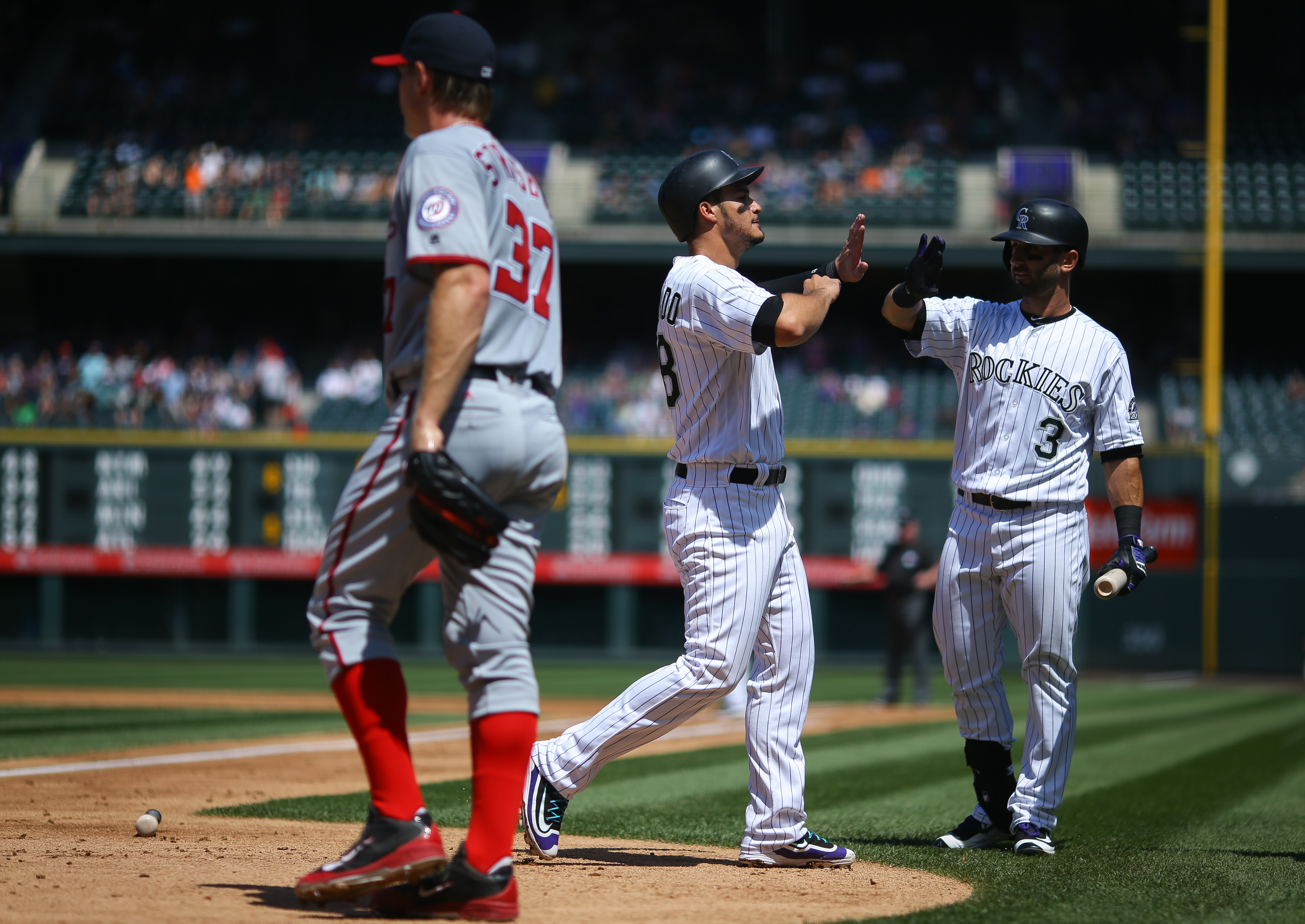 DENVER, CO - AUGUST 17: Nolan Arenado #28 of the Colorado Rockies is congratulated by Daniel Descalso #3 after scoring during the first inning as starting pitcher Stephen Strasburg #37 of the Washington Nationals walks back to the mound at Coors Field on August 17, 2016 in Denver, Colorado. (Photo by Justin Edmonds/Getty Images)