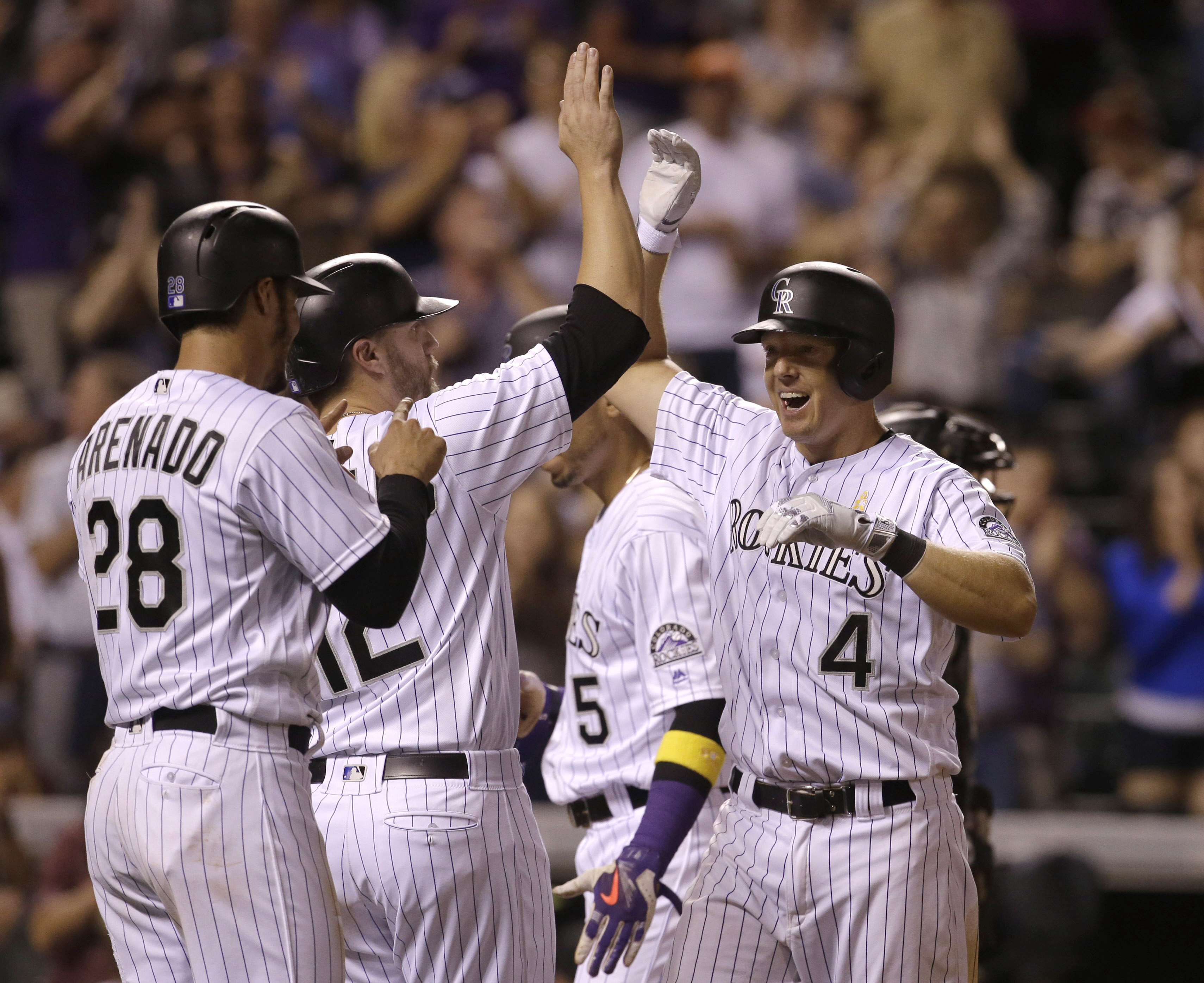 .Nick Hundley #4 of the Colorado Rockies celebrates at home plate after his grand slam home run with teammates Nolan Arenado #28 of the Colorado Rockies, Mark Reynolds #12 of the Colorado Rockies and Carlos Gonzalez #5 of the Colorado Rockies against the Arizona Diamondbacks in the eighth inning  at Coors Field on September 2, 2016 in Denver, Colorado. (Photo by Joe Mahoney/Getty Images)