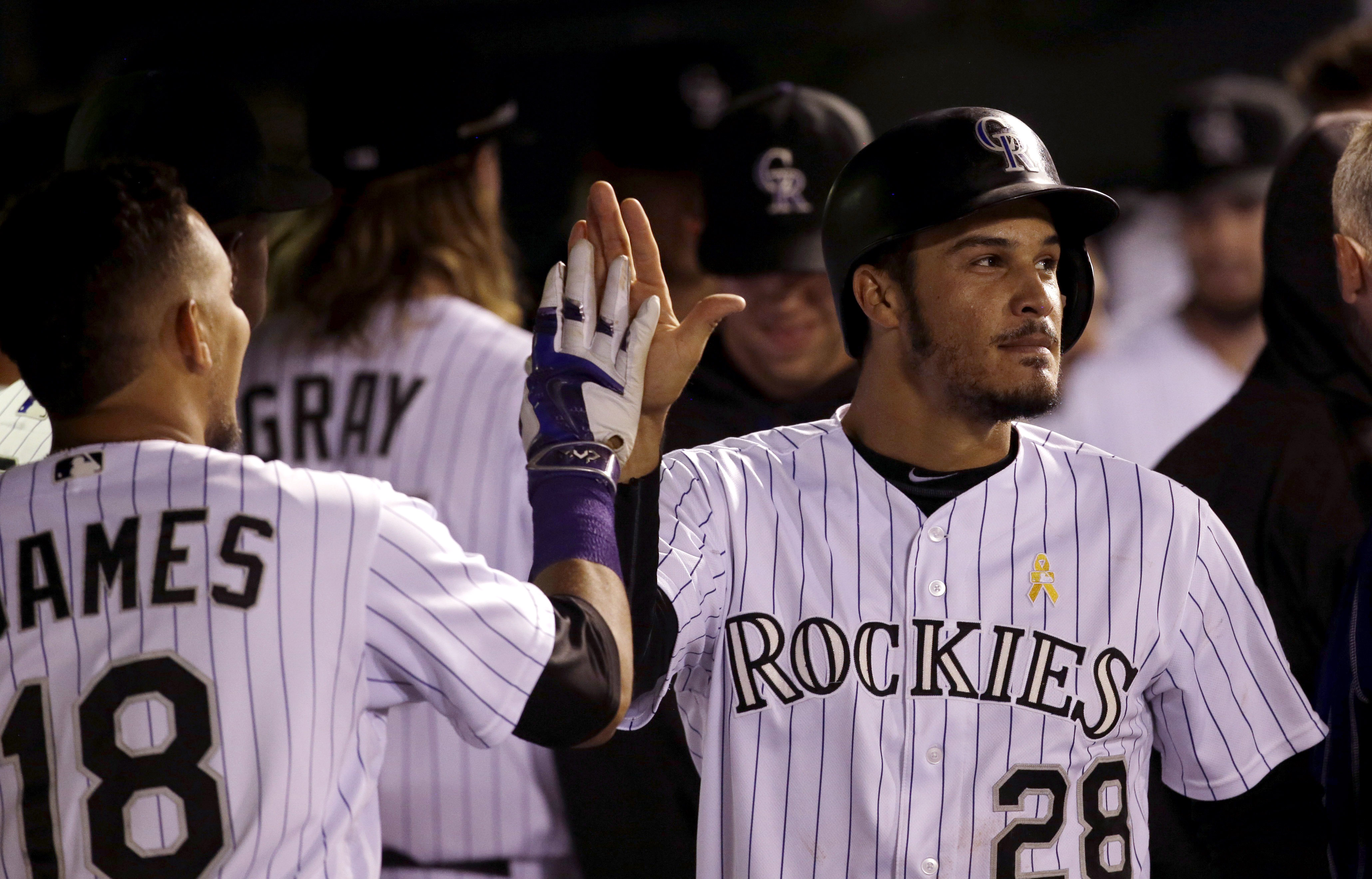 Cristhian Adames #18 of the Colorado Rockies congratulates Nolan Arenado #28 of the Colorado Rockies after Arenado scored in the fourth inning against the Arizona Diamondbacks during a baseball game at Coors Field on September 2, 2016 in Denver, Colorado. (Photo by Joe Mahoney/Getty Images)