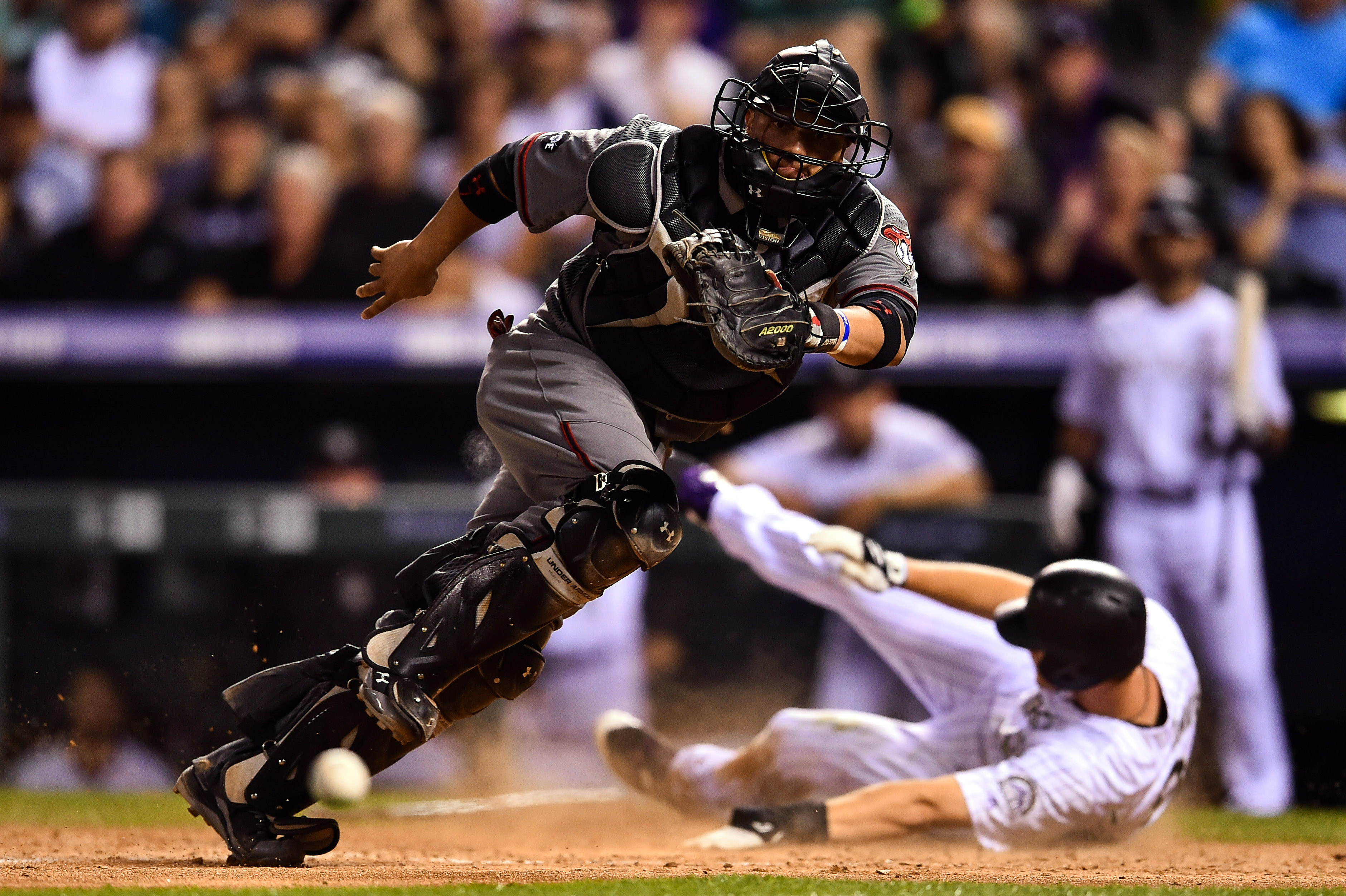 Welington Castillo #7 of the Arizona Diamondbacks moves to field a putout attempt as DJ LeMahieu #9 of the Colorado Rockies slides safely across home plate to score in the sixth inning of a game at Coors Field on September 3, 2016 in Denver, Colorado.  (Photo by Dustin Bradford/Getty Images)