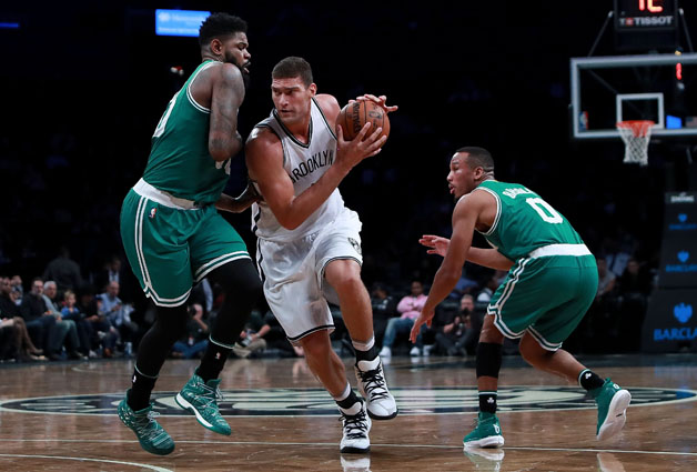 Brook Lopez #11 of the Brooklyn Nets splits the defense of Amir Johnson #90 and Avery Bradley #0 of the Boston Celtics during the first half of the preseason game at Barclays Center on October 13, 2016 in New York City.