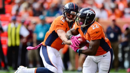 Quarterback Paxton Lynch #12 of the Denver Broncos hands the ball off to C.J. Anderson #22 in the first quarter of the game against the Atlanta Falcons at Sports Authority Field at Mile High on October 9, 2016 in Denver, Colorado.