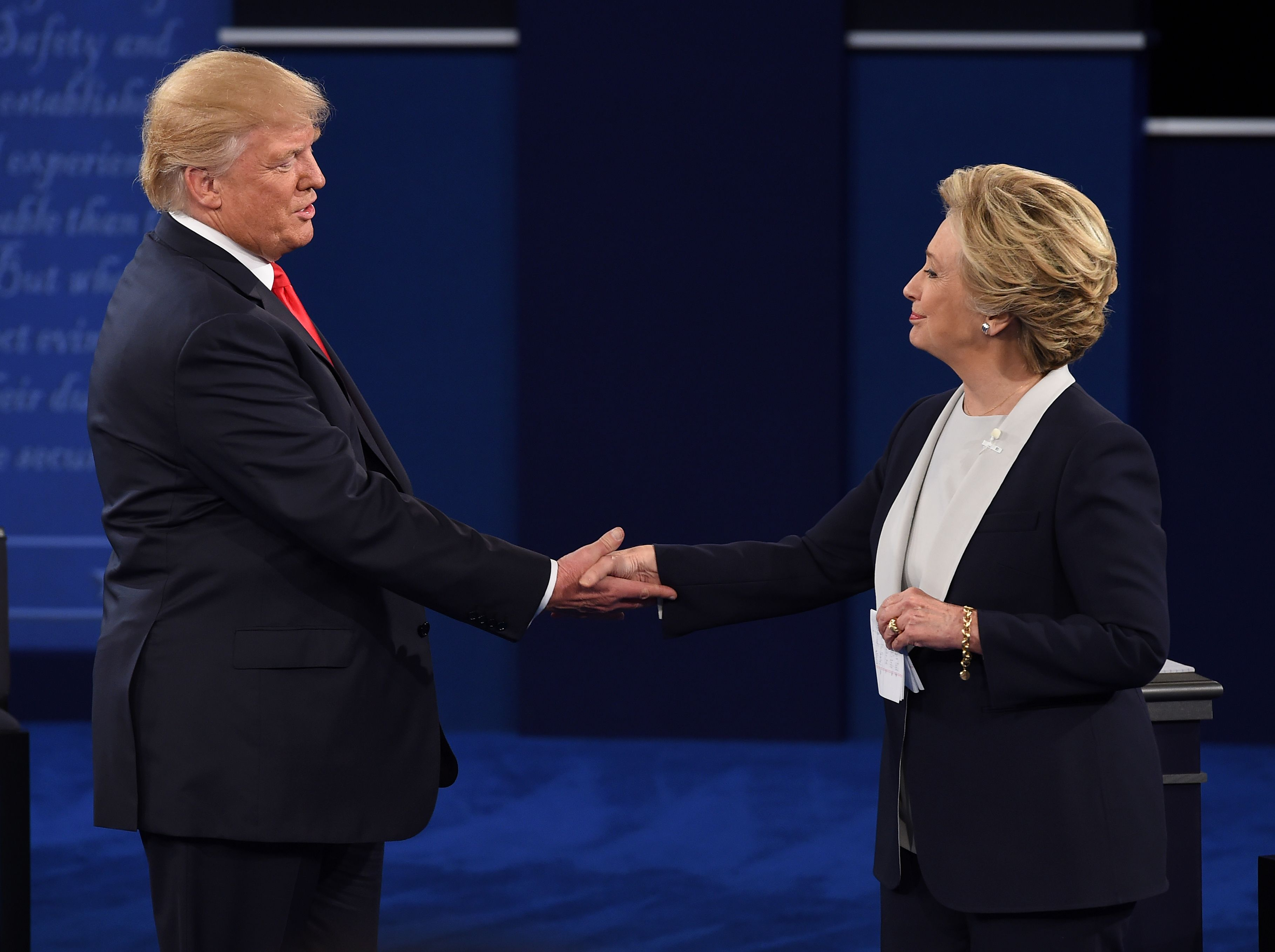 US Democratic presidential candidate Hillary Clinton (R) and US Republican presidential candidate Donald Trump at the end of the second presidential debate at Washington University in St. Louis, Missouri. (Photo credit should read ROBYN BECK/AFP/Getty Images)