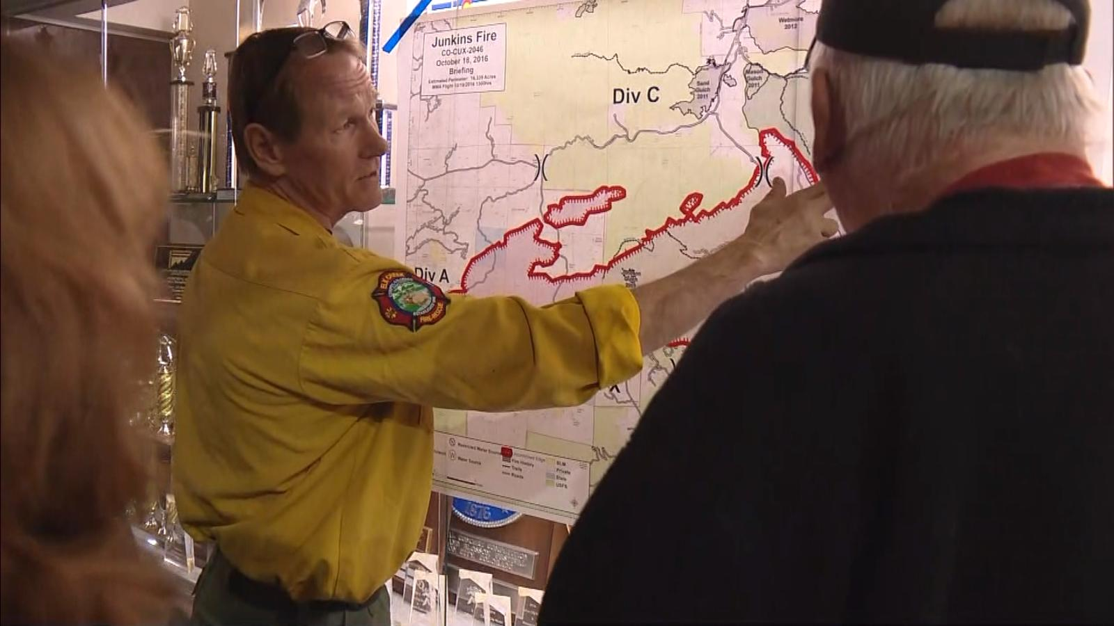 A wildland official shows a resident the map of the Junkins Fire on Oct. 19, 2016. (credit: CBS)