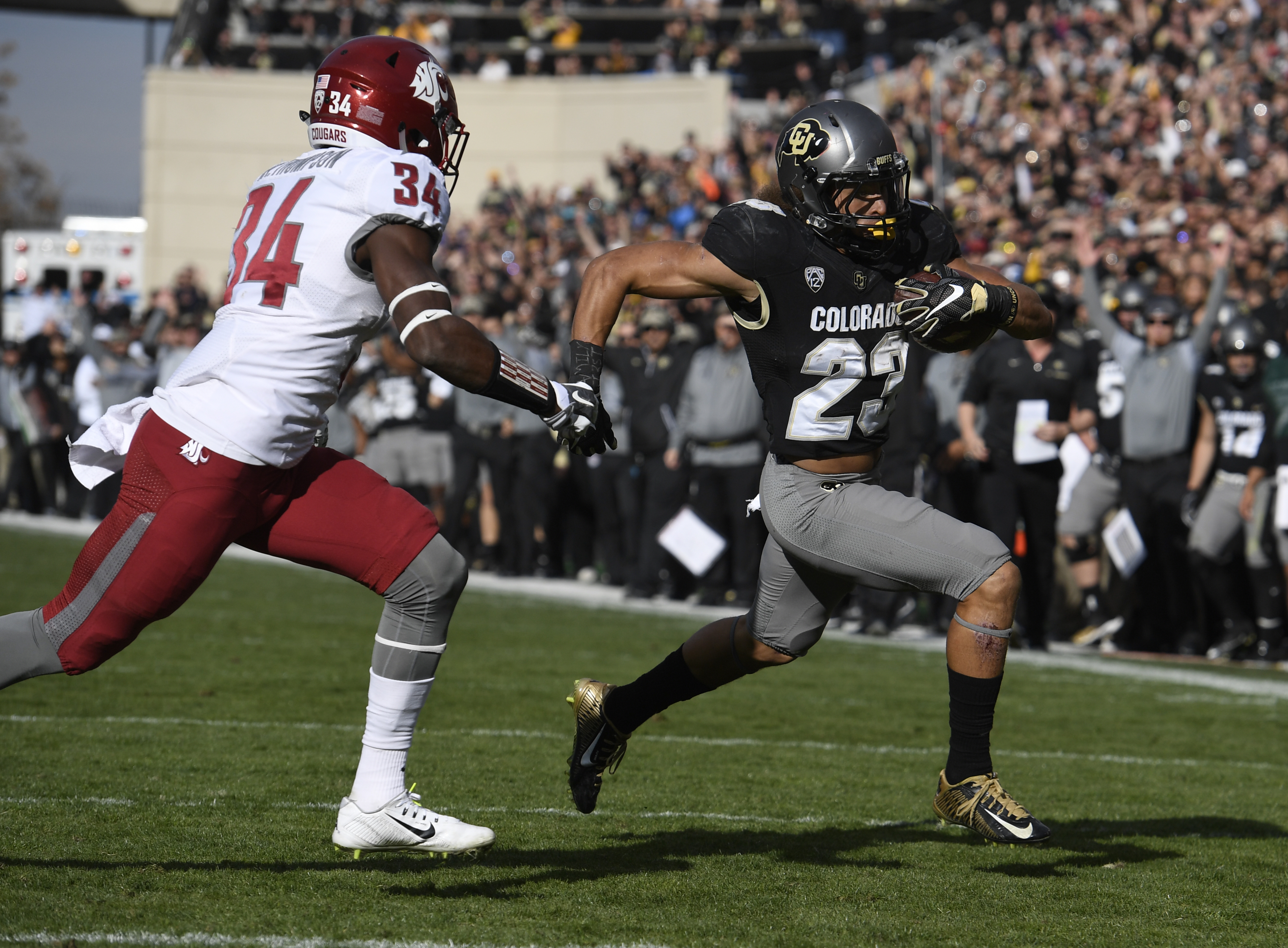 Colorado Buffaloes running back Phillip Lindsay gets past Washington State Cougars safety Jalen Thompson to score a touchdown in the first quarter at Folsom Field Nov. 19, 2016. (Photo by Andy Cross/The Denver Post via Getty Images)