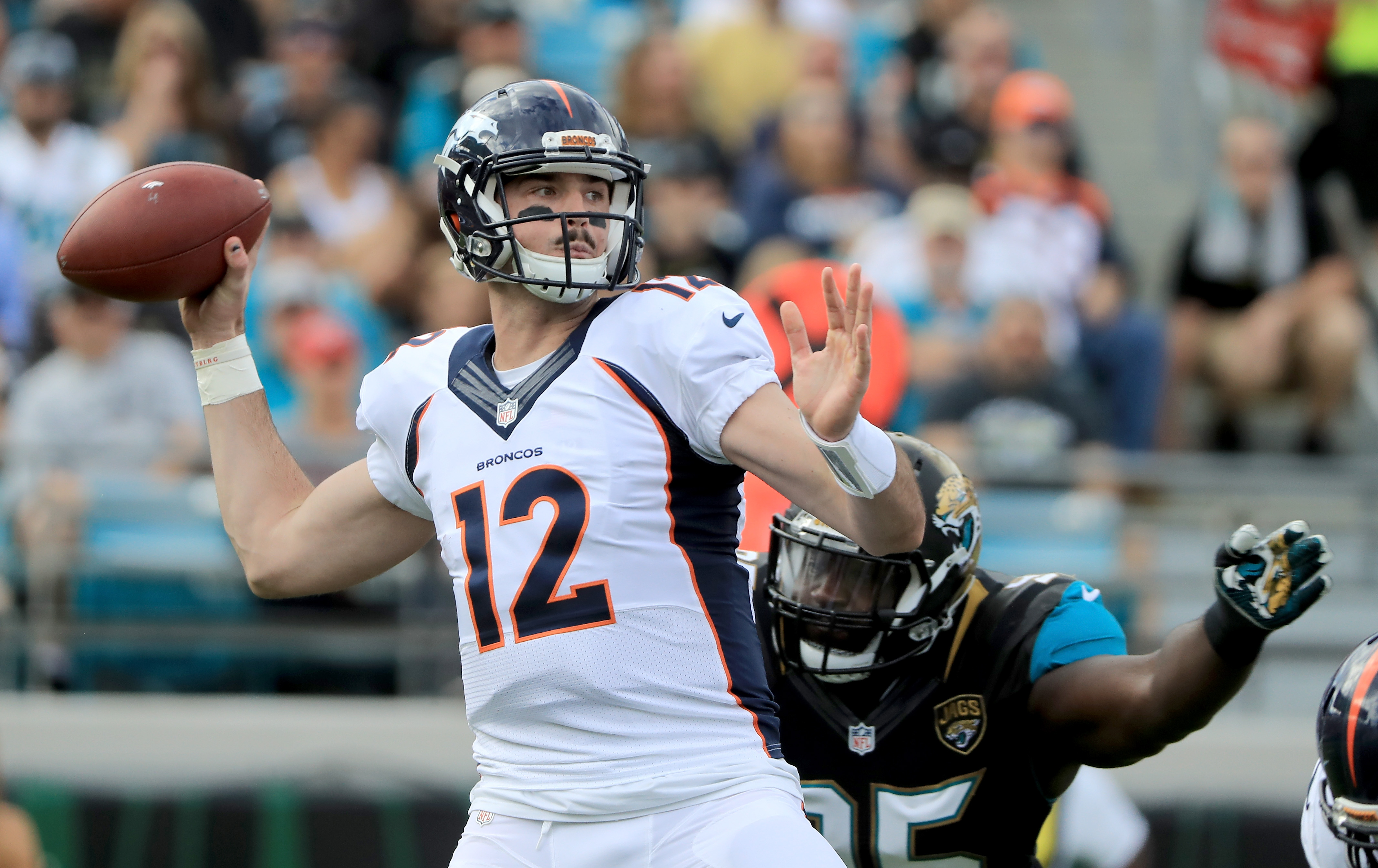 Paxton Lynch #12 of the Denver Broncos attempts a pass as Abry Jones #95 of the Jacksonville Jaguars closes in at EverBank Field on December 4, 2016 in Jacksonville, Florida. (Photo by Sam Greenwood/Getty Images)