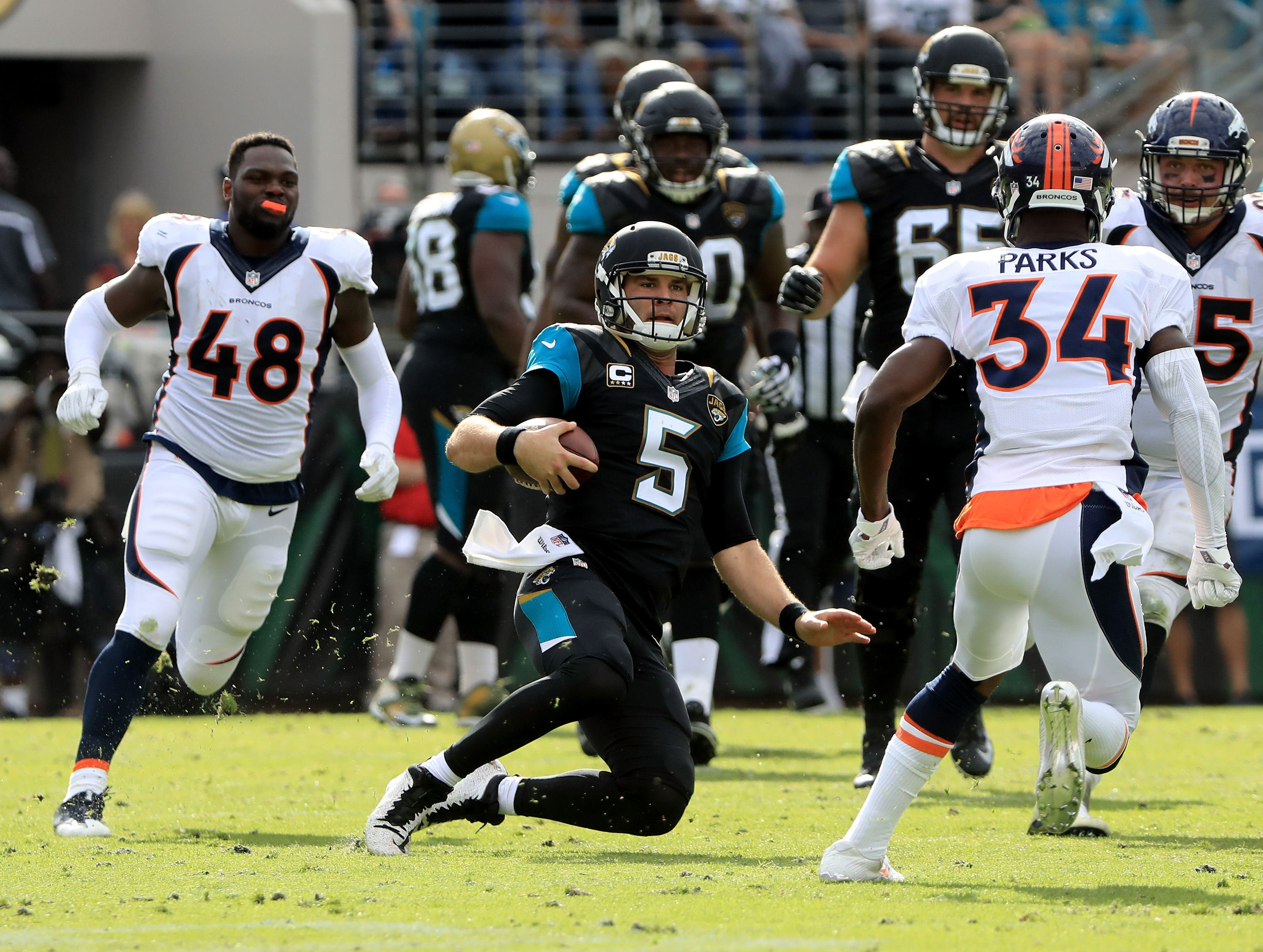 JACKSONVILLE, FL - DECEMBER 04: Blake Bortles #5 of the Jacksonville Jaguars slides after running for yardage as Shaquil Barrett #48 and Will Parks #34 of the Denver Broncos close in at EverBank Field on December 4, 2016 in Jacksonville, Florida. (Photo by Sam Greenwood/Getty Images)