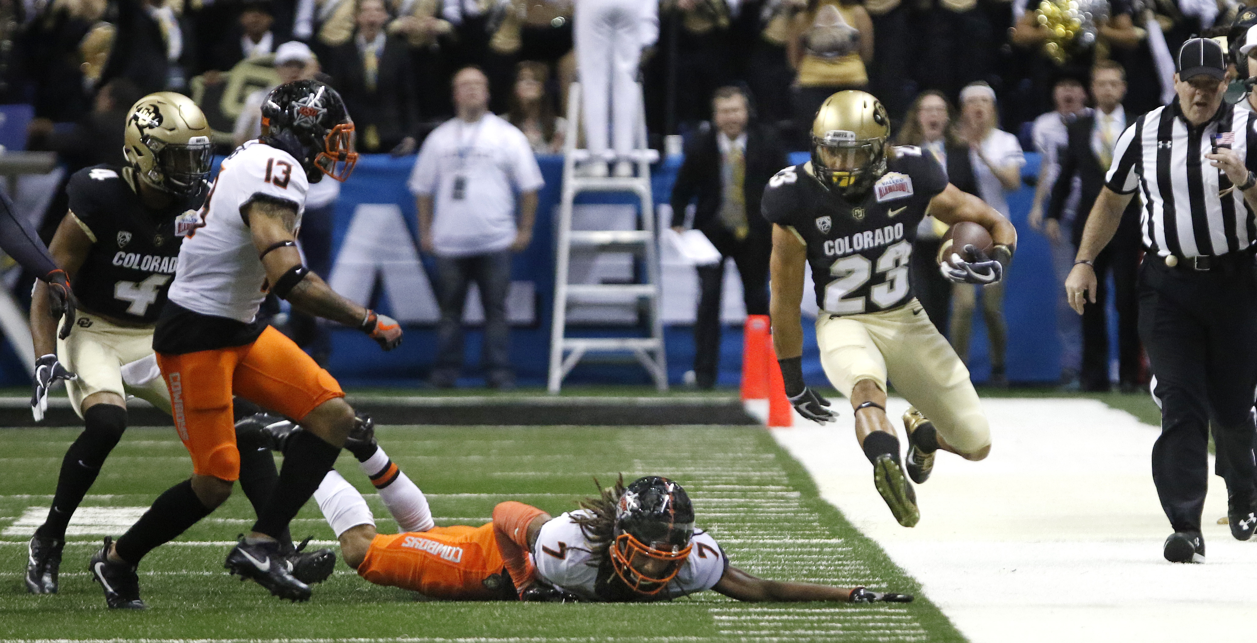 SAN ANTONIO,TX - DECEMBER 29: Ahkello Witherspoon #23 of the Colorado Buffaloes leaps over the would be tackle of Ramon Richards #7 of the Oklahoma State Cowboys in the Valero Alamo Bowl at the Alamodome on December 29, 2016 in San Antonio, Texas. (Photo by Ronald Cortes/Getty Images)