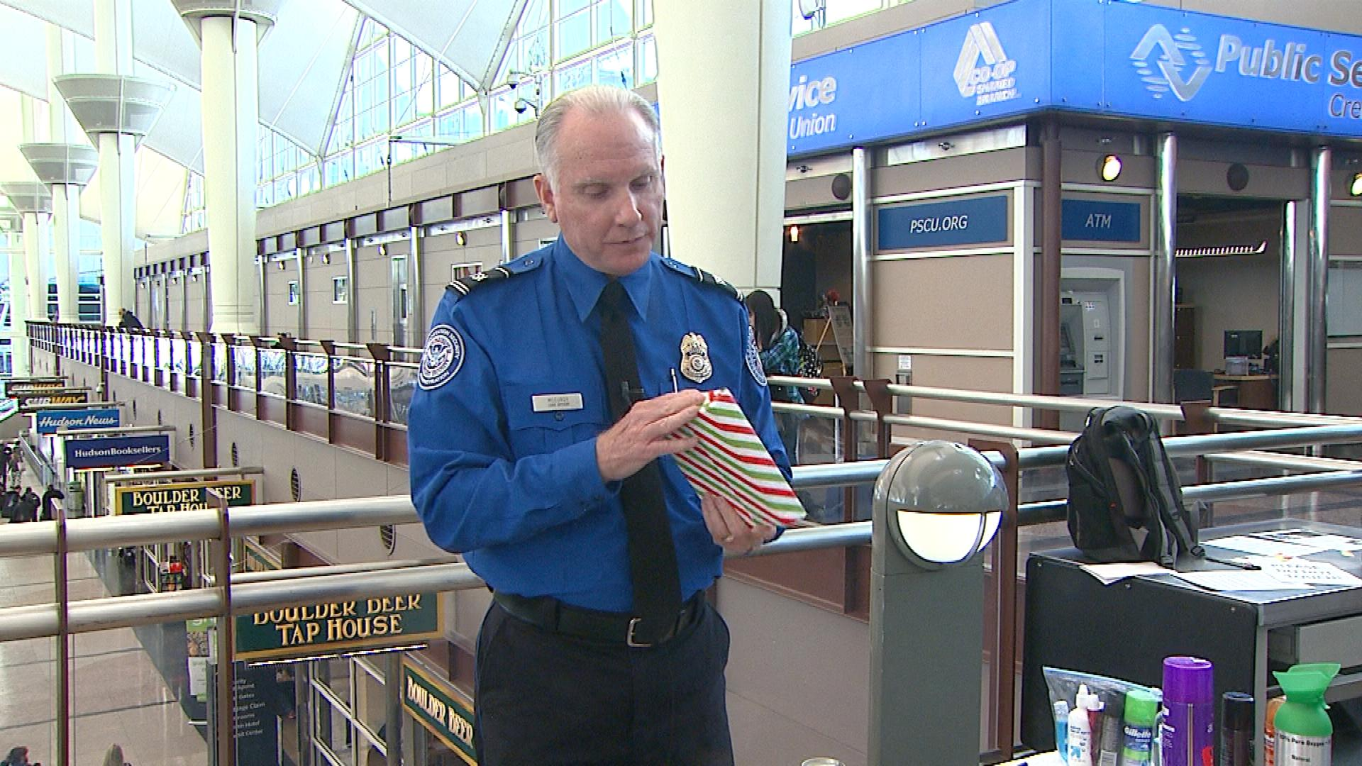 Harold McCurdy with TSA with a wrapped present (credit: CBS)