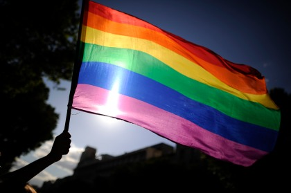 File photo of a person waving a rainbow flag. (Photo by PEDRO ARMESTRE/AFP/GettyImages)