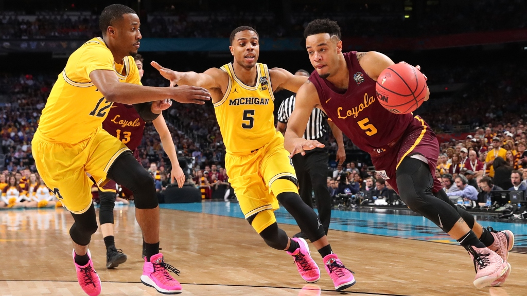 Marques Townes #5 of the Loyola Ramblers is defended by Muhammad-Ali Abdur-Rahkman #12 and Jaaron Simmons #5 of the Michigan Wolverines in the first half during the 2018 NCAA Men's Final Four Semifinal at the Alamodome on March 31, 2018 in San Antonio, Texas.
